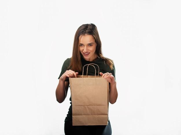 여자는 흰색 바탕에 식료품 쇼핑 가방을 들고 있다. 손에 밝은 갈색 종이 가방. 격리 된 배경입니다.