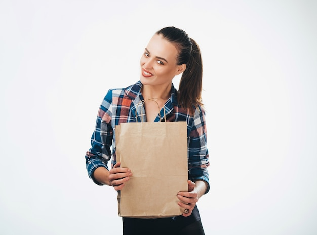 Woman is holding grocery shopping bag on white background. paper bags in hands. isolated background.