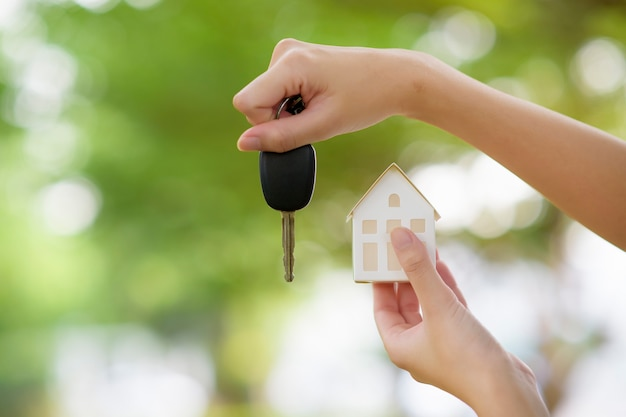 Woman is holding house and car key on green