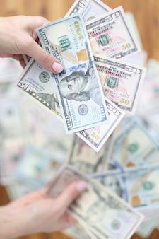 Женщина держит много наличных американских денег, большие инвестиции и концепция роста доходов