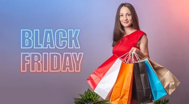 여자가 쇼핑백을 들고 있고 옆에 블랙 프라이데이라는 단어가 적혀 있습니다.