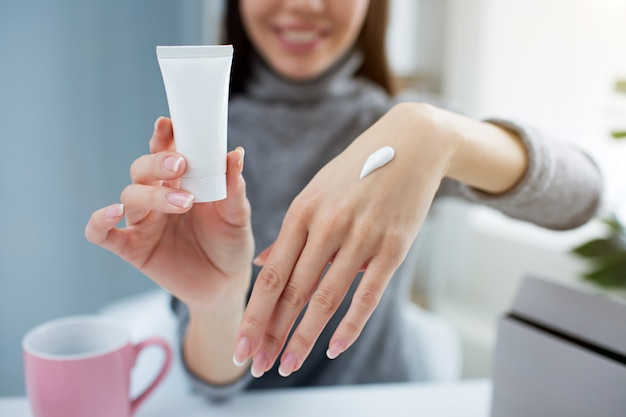 Woman is holding a small tube with hand cream in one hand and showing her other hand with some cream on it