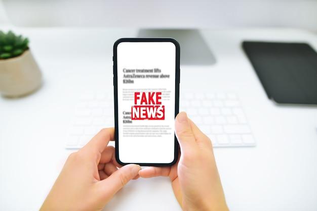 女性はスマートフォンを持ってインターネット上で偽のニュースを読んでいます。プロパガンダ、誤報、デマの概念。