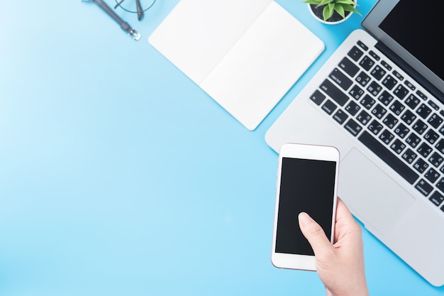 A woman is holding a smartphone isolated with a minimal blue deskcopy space, flat lay, top view, mock up