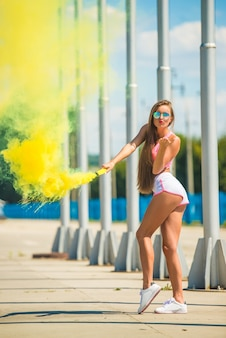 Woman is holding smoke bomb and blowing a kiss outdoor.