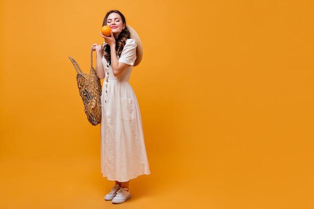 La donna sta tenendo la borsa della stringa e l'arancio. sorrisi svegli della ragazza castana su fondo arancio.