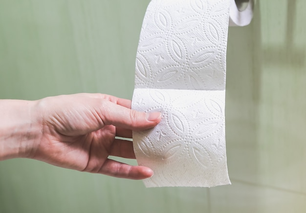 Woman is holding toilet paper in her hand.