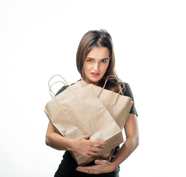 여자는 흰색 바탕에 두 개의 식료품 쇼핑 가방을 들고 있다. 얼굴 근처에 종이 봉지. 격리 된 배경입니다.