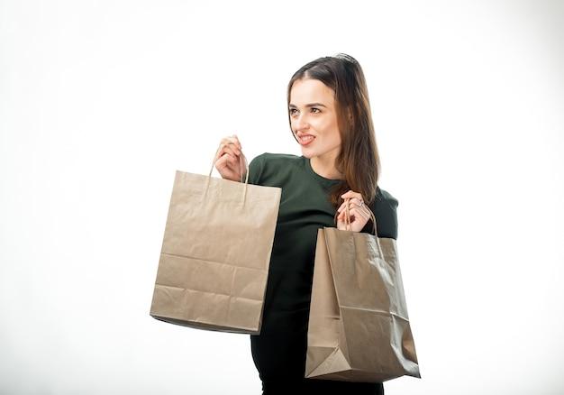 여자는 흰색 바탕에 두 개의 식료품 쇼핑 가방을 들고 있다. 손에 종이 가방. 격리 된 배경입니다.