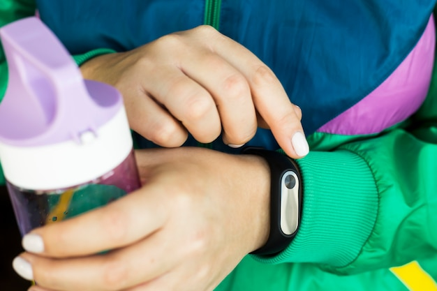 A woman is holding a water bottle for fitness and a fitness bracelet. in a sports bright green jacket for sports. healthy lifestyle and fitness concept