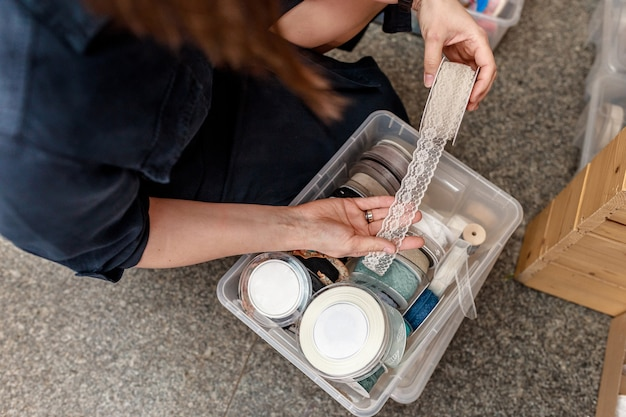 Женщина держит белую кружевную ленту для украшения и поделок. концепция подарков и украшений своими руками. сделай сам