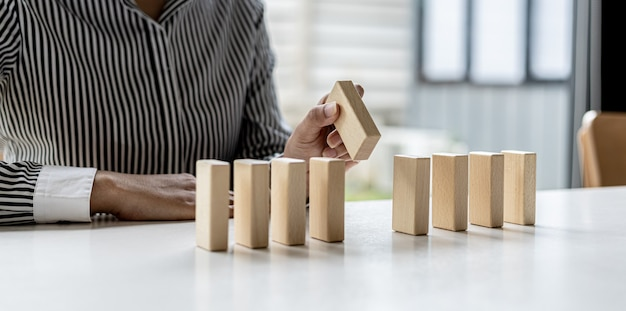 A woman is holding wooden blocks in a row, she grabs the center piece to complete them, the wooden block arrangement conveys the business operation by efficient management. business idea.