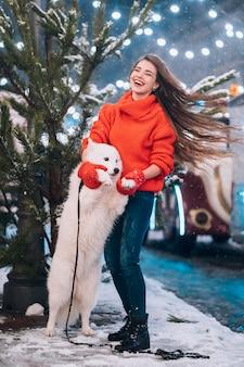 여자는 밤 거리에 그녀의 강아지를 포옹