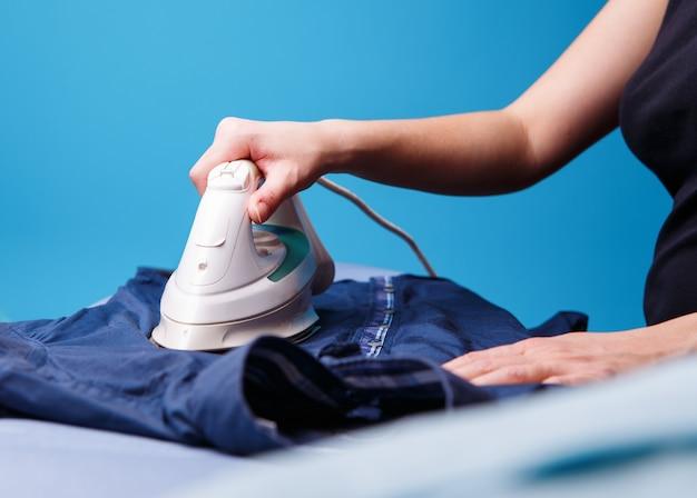 女性が男性のシャツにアイロンをかけている。家事のコンセプト。
