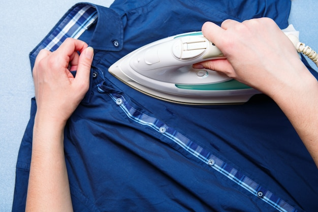 女性が男性のシャツにアイロンをかけている。上面図。家事のコンセプト。