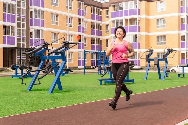 Женщина бегает на спортивной площадке во дворе городского дома