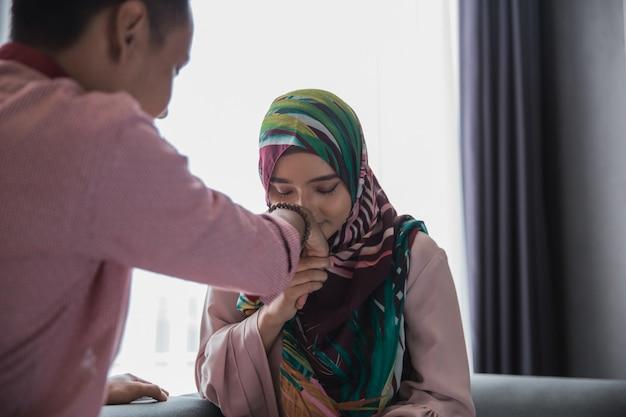 Женщина целует руку мужа