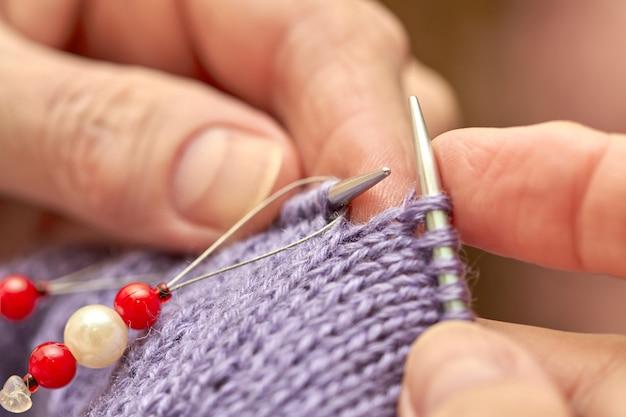 Женщина вяжет голубой теплый свитер