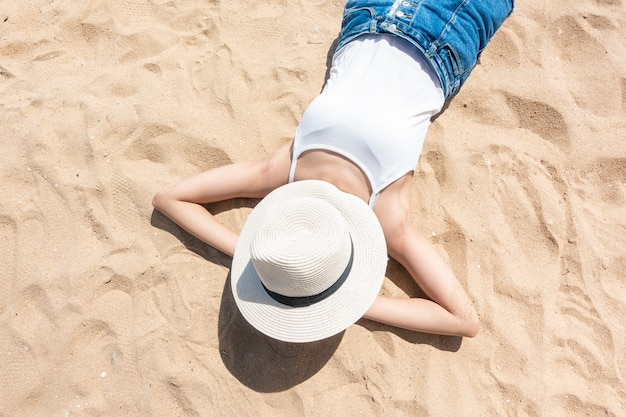 A woman is laying on the beach