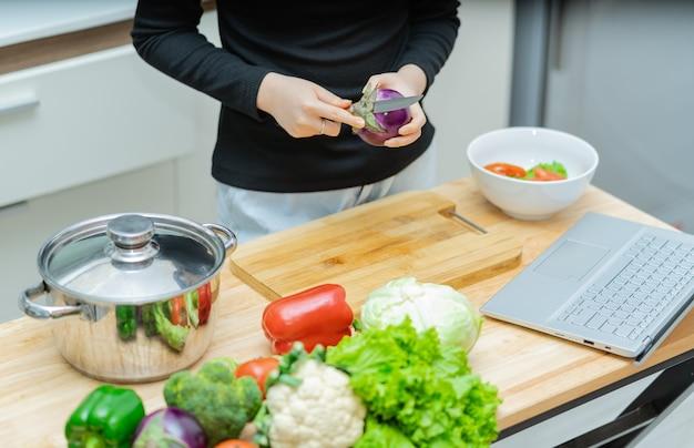 女性が自宅で一人で料理を学んでいるオンライン料理コース