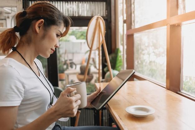 여자가 태블릿을 보고 카페에서 커피를 마시고 있다