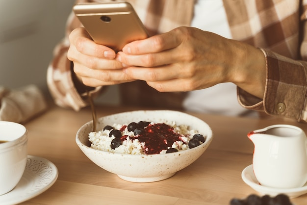 Woman is looking for information on internet, using mobile, during eating breakfast. concept for digital addiction. blogger taking photos of food, shooting breakfast