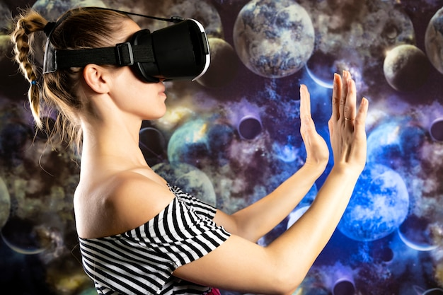 A woman is looking through virtual reality at space. space background