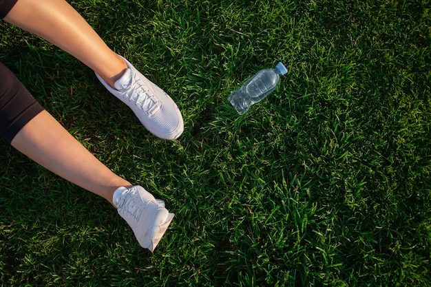 Woman is lying on the green lawn in the park. happy woman relaxing on the grass during sunny summer day. women's feet in white sneakers. top view. large format banner