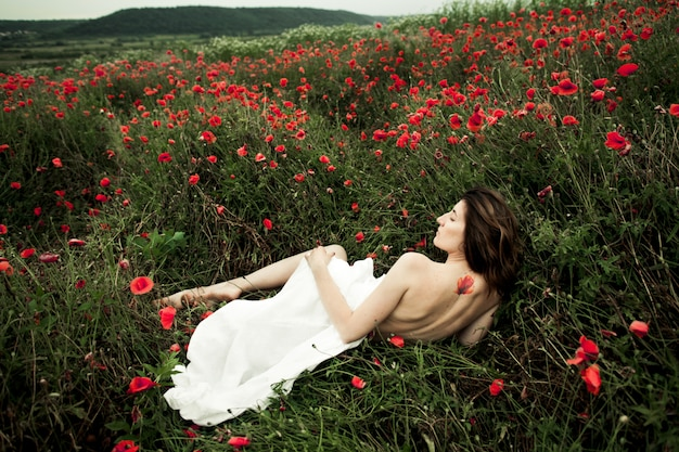 Woman is lying naked covered a white shirt among poppy flowers