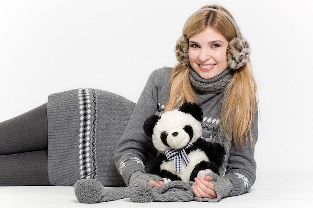 女性は毛皮のヘッドフォンとパンダのおもちゃで白い背景に横たわっています