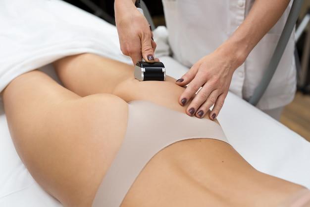 Женщина лежит на диване в косметологической клинике и ей делают вакуумный массаж с помощью специального медицинского устройства. аппаратная косметология. уход за телом