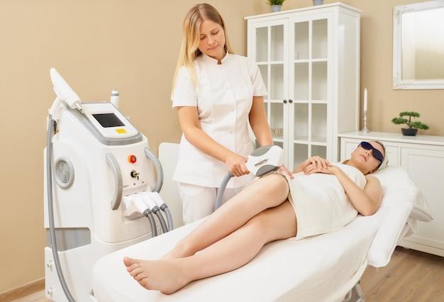 Женщина лежит на кушетке в медицинских очках в процедурном кабинете.