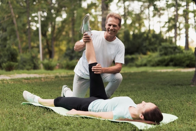 Woman is lying on a rug for yoga, a man is holding her leg