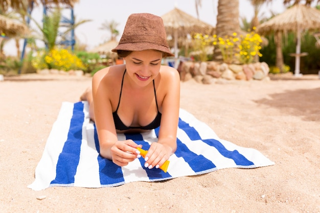 Woman is lying on striped towel on the sand and applying sun cream on her hand.