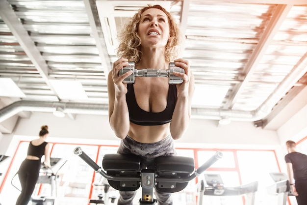 A woman is lying on a training apparatus. she is holding a dumbell.