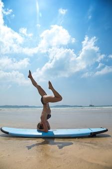 A woman is making a headstand, sirsasana