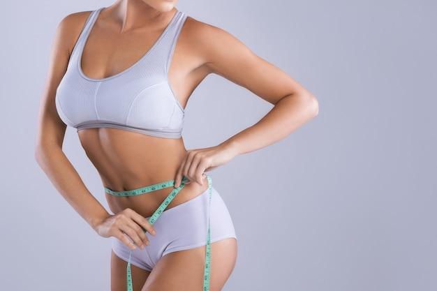 Woman is measuring her waistline