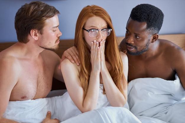 여자는 두 남자에게 성추행을 당하고 수줍어하고 두려워합니다.