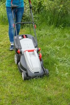 여자는 봄날 정원에서 잔디 깎는 기계로 작업하고 있습니다. 잔디 깎는 기계. 정원사 관리 작업 도구를 깎습니다.