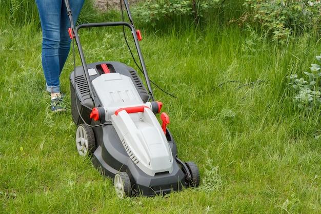 여자는 화창한 여름날 정원에서 잔디 깎는 기계로 작업하고 있습니다. 잔디 깎는 기계. 정원사 관리 작업 도구를 깎습니다.