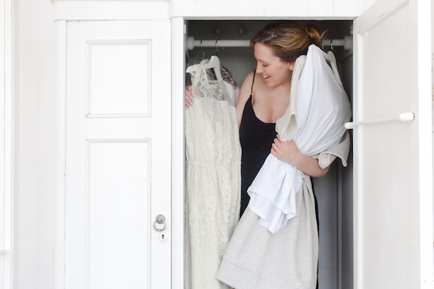 A woman is overwhelmed in closet of messy clothes