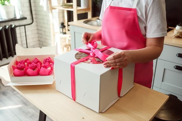 女性は箱のパッケージのピンクのカップケーキを箱に大きなバースデーケーキを詰めています
