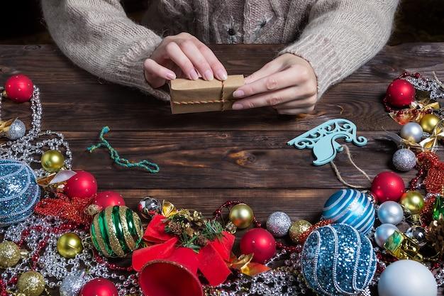 女性はクリスマスの装飾が施された暗い木製のテーブルにクリスマスプレゼントを詰めています