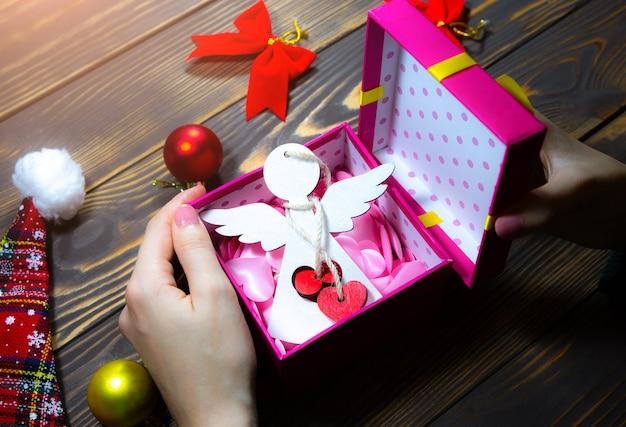 女性はクリスマスプレゼントを詰めています。心の中の木の天使。木製のテーブルの装飾。明けましておめでとうございます。居心地の良いムードとお祭りの時間。スペースの場所をコピーします。