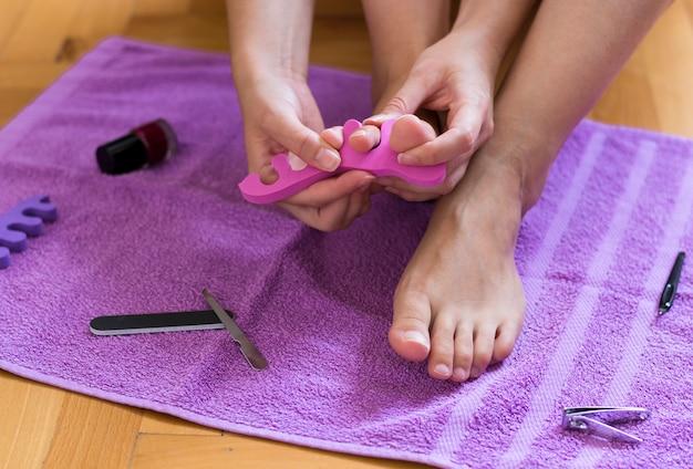 女性は自宅で彼女の足の爪を塗っている