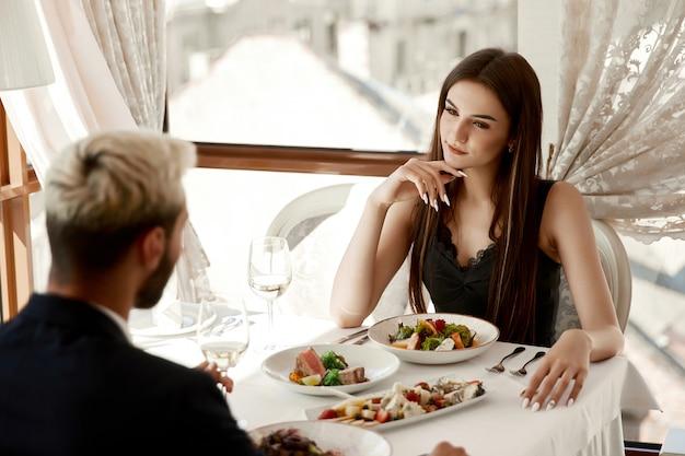 여자는 열정적으로 레스토랑에서 잘 생긴 찾고있다