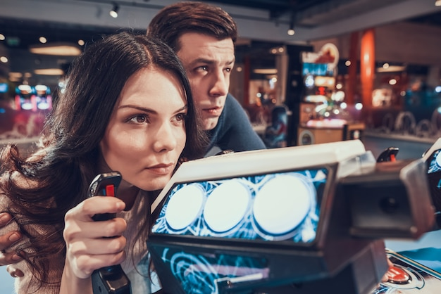 Woman is piloting spacecraft playing in arcade.