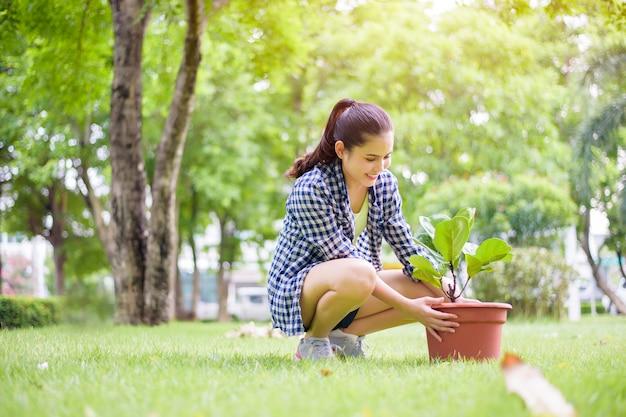 Женщина сажает дерево в саду