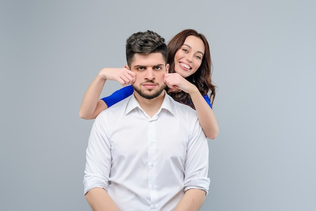Woman is playing with her boyfriend and annoying him isolated over grey background