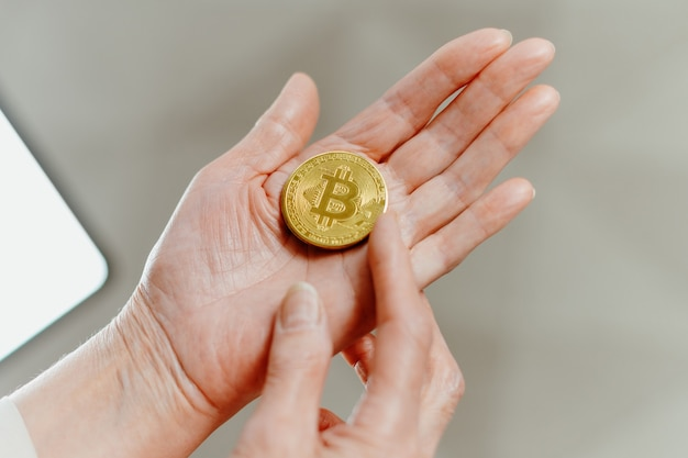 Woman is pointing at the bitcoins in her palm Premium Photo